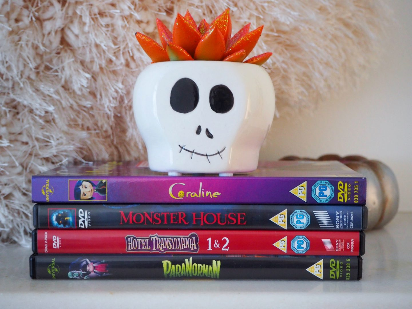 10 Halloween Movies If You Aren't A Fan Of Horror - dvd stack with skull succulent