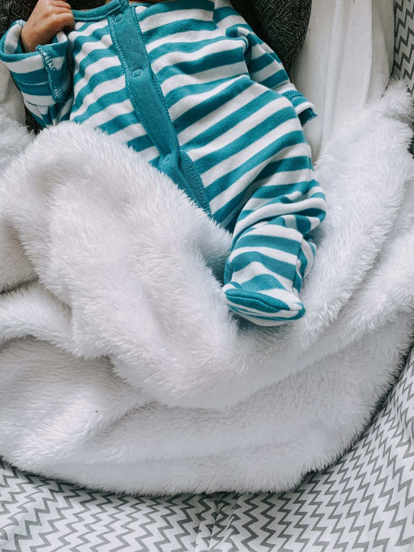20 Things They Don't Tell You About Motherhood - baby in basket wearing striped sleep suit