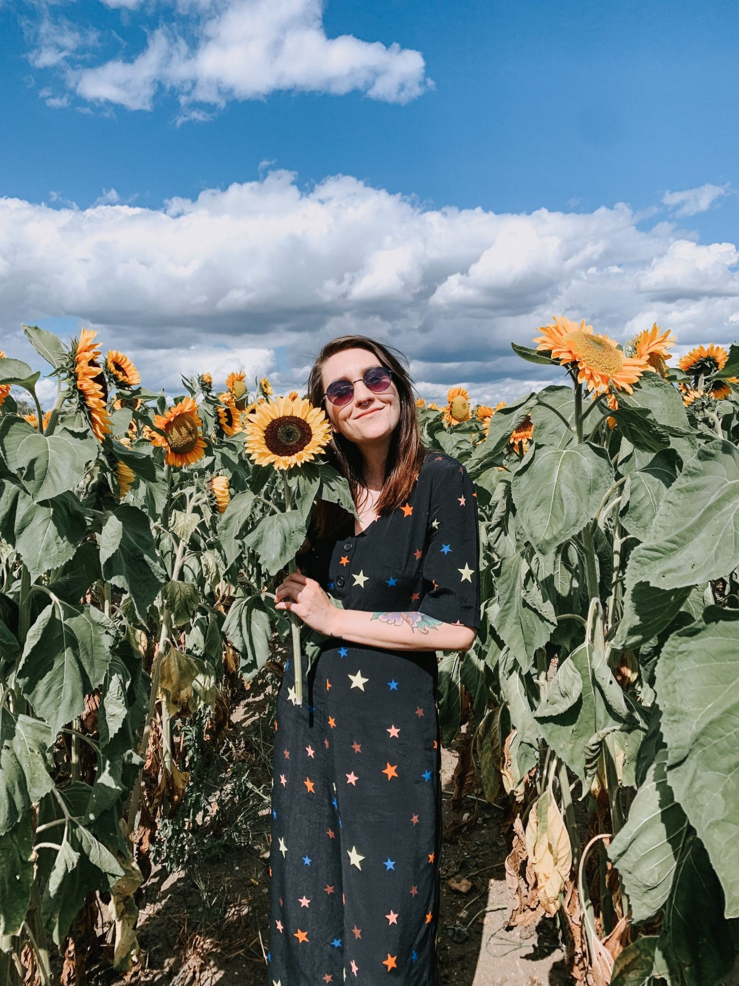 Goodbye To Fast Fashion - outfit in sunflower field; star jumpsuit